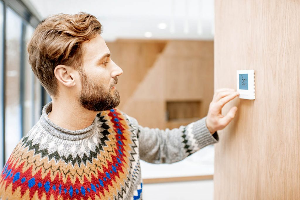 Man in sweater adjusts thermostat